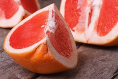 Pieces of red grapefruit on the old wooden table closeup Royalty Free Stock Photo