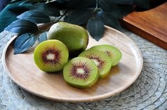 Pieces of Red Kiwifruit on Plate with Green Leaves on Background. Pieces of fresh red kiwifruit on wooden plate with green leaves on background royalty free stock images