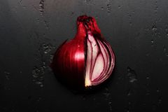 Pieces of red onion in close up. Onion halves. Placed on dark texture background. Vegetable in purple color cut in pieces. Food and healthy diet concept royalty free stock photo