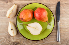 Pieces red pears in green plate and knife on table Royalty Free Stock Photo