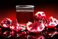 Pieces of red pomegranate and pomegranate juice on a black background Stock Photos