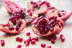 Pieces of red pomegranate on the wooden background Royalty Free Stock Image