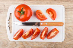 Pieces of red tomatoes and kitchen knife on cutting board Stock Photos