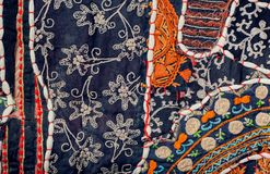 Pieces of retro cloth in patchwork style. Patterns on texture of vintage blanket surface with flowers Stock Photos