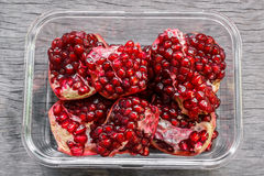 Pieces of ripe juicy pomegranate in a rectangular glass. Stock Photography
