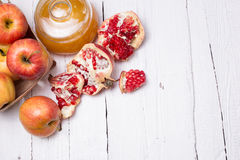 Pieces ripe pomegranate, honey and apple Royalty Free Stock Images