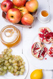 Pieces ripe pomegranate, honey, grapes and apple Stock Images