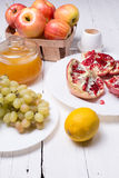 Pieces ripe pomegranate, honey, grapes and apple Stock Image