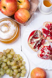 Pieces ripe pomegranate, honey, grapes and apple Royalty Free Stock Photography