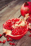 Pieces of ripe pomegranate on wooden table Royalty Free Stock Images