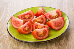 Pieces of ripe red tomatoes in green plate on table Royalty Free Stock Images