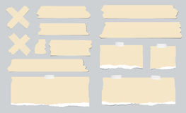 Pieces of ripped brown blank note paper, sticky, adhesive tapes are stuck on gray wall Royalty Free Stock Images