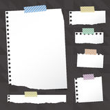 Pieces of ripped white notebook paper are stuck with sticky tape on black pattern. Royalty Free Stock Images