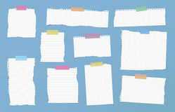 Pieces of ripped white ruled note paper are stuck with colorful sticky tapes on blue background Stock Photo