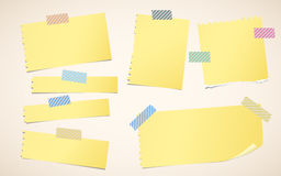 Pieces of ripped yellow blank notebook paper are stuck with striped sticky tape Royalty Free Stock Photos