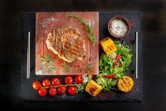 Pieces of roast beef with spices served on black slate. stock photography
