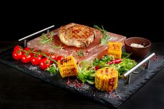 Pieces of roast beef with spices served on black slate. royalty free stock photo