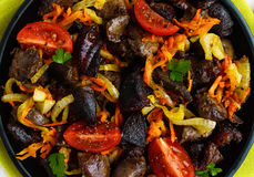 Pieces of roast duck, goose meat, liver, heart with vegetables onion, carrot, tomato, with spices on a round cast-iron frying Stock Photography