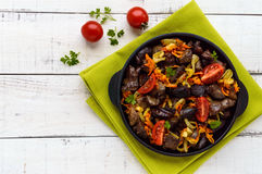 Pieces of roast duck, goose meat, liver, heart with vegetables onion, carrot, tomato, with spices Stock Photography