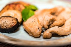 Pieces of roasted chicken and vegetables on plate. Close up plate with pieces of roasted chicken fillet and vegetables, healthy food concept. Selective focus Stock Photos