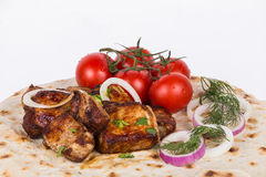 Pieces of roasted meat with vegetables. grilled meat with tomatoes and greens on a pita Royalty Free Stock Image