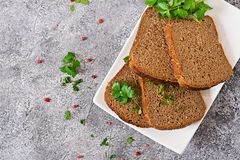 Pieces of rye bread on a plate. Top view. Grey background stock photography