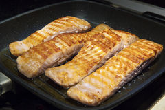 Pieces Salmon in a Pan. Cooking pieces of a fish Salmon in hot pan on kitchen stove. The meat is with a golden frying crust Royalty Free Stock Photo