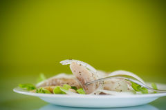Pieces of salted herring with onions. And spices Stock Photos