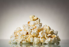 Pieces of salty popcorn on a gray Royalty Free Stock Photos