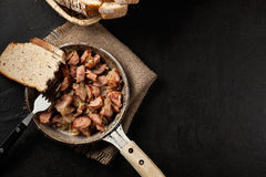 Pieces of sausage fried with onions Royalty Free Stock Images