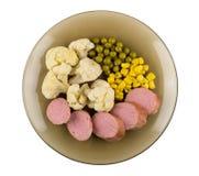Pieces of sausages, cauliflower, sweet corn, green peas on white Royalty Free Stock Photos