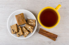 Pieces of sherbet, cup of tea and cinnamon sticks Stock Photos