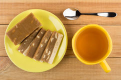 Pieces of sherbet with nuts in yellow saucer and tea Royalty Free Stock Images