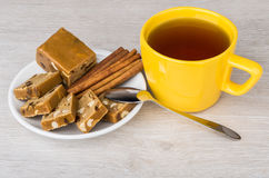 Pieces of sherbet in saucer, cup of tea, cinnamon sticks Royalty Free Stock Image