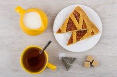 Pieces of shortbread pie, milk jug, sugar and tea Royalty Free Stock Photo