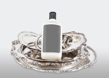 Pieces of silver and a bottle of polishing product Royalty Free Stock Photos