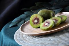 Pieces of Sliced Red Kiwifruit on Plate. Pieces of sliced red kiwifruit on wooden plate royalty free stock images