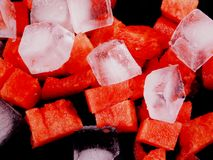 Pieces of sliced watermelon with pieces of ice abstraction background. Slices of watermelon and ice cubes on a black plate scattered Stock Photography