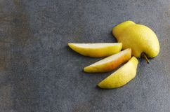 Pieces of sliced yellow ripe pear on dark surface at the restaurant before presentation to guest.Copy space stock photography