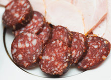 Pieces of smoked sausage on a plate. Nutrient food Royalty Free Stock Photography