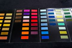 Pieces of soft textile fabric of different colors glued to the c. Atalog of samples for customer choice with the ability to touch and feel the quality of the Royalty Free Stock Photo