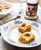 Pieces of sweet baklava on the plate, green garden background Royalty Free Stock Image