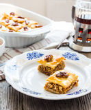 Pieces of sweet baklava on the plate, green garden background Royalty Free Stock Photography