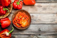 Pieces of sweet pepper in a bowl and a whole pepper in a basket. On wooden background stock photos