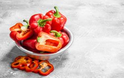 Pieces of sweet pepper and whole red peppers in the bowl. On rustic background royalty free stock photography