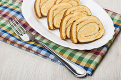 Pieces of swiss roll cake in dish and fork Royalty Free Stock Photo