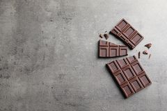 Pieces of tasty chocolate on grey background, flat lay. Space for text royalty free stock image