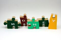 Pieces to the money puzzle. Jigsaw puzzle pieces for trying to understand the money puzzle Royalty Free Stock Photography