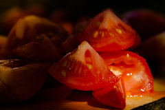 Pieces of tomatoes on a wooden board. Low light and shallow dept Royalty Free Stock Photo