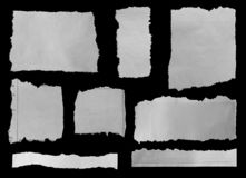 Torn papers on black. Pieces of torn newspaper on black background royalty free stock photography